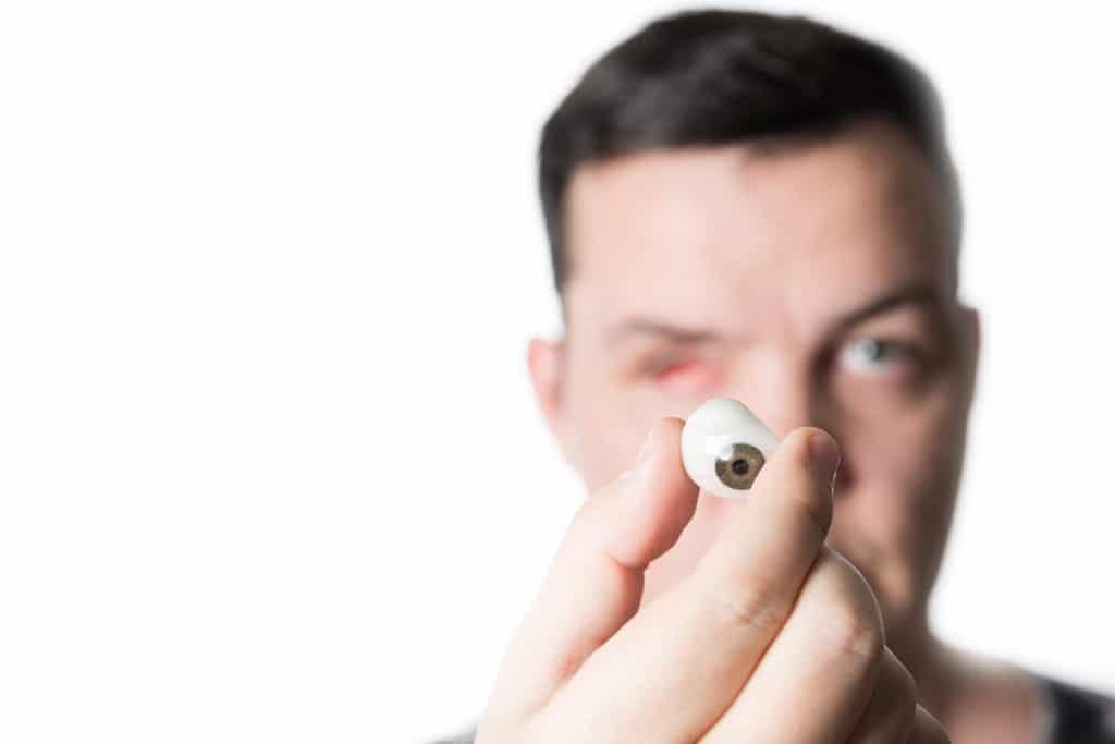 Mann hält Glasauge in seiner Hand